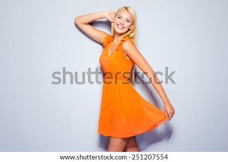 Spring is in my heart. Beautiful young woman in pretty dress holding hand behind head and smiling while standing against grey background   - stock photo