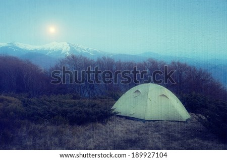 Spring landscape at night. Camping in the mountains in the moonlight. Tent in the mountains. Carpathians, Ukraine, Europe. Filtered image: vintage, grunge and texture effects - stock photo