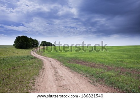 spring landscape dirt road of endless fields and beautiful clouds in the blue sky - stock photo