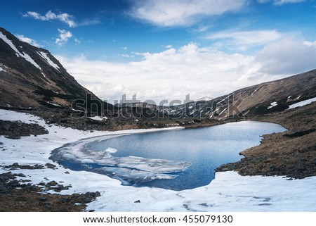 Spring landscape. Mountain lake with ice and snow on the shore. Overcast day - stock photo