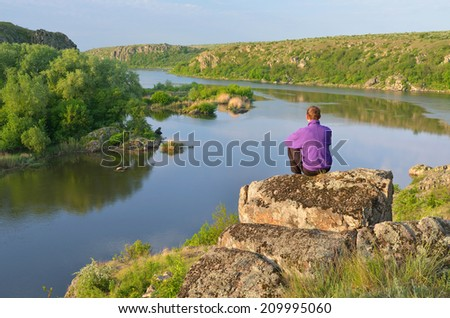 Spring landscape sunny day. A man sits on a stone and looking at the river - stock photo
