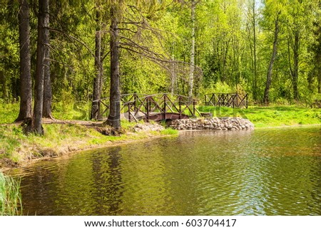 Spring landscape with forest lake and small wooden bridge