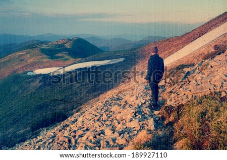 Spring landscape with man tourist on a mountain trail. Carpathians, Ukraine, Europe. Filtered image: vintage, grunge and texture effects - stock photo
