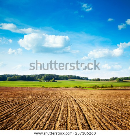 Spring Landscape with Plowed Field on the Background of Beautiful Clouds and Blue Sky. Ploughed Soil. Agriculture Concept. Copy Space. - stock photo