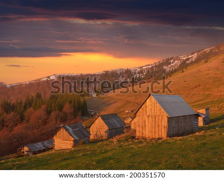 Spring landscape with wooden village of shepherds in the mountains. Light of the setting sun - stock photo