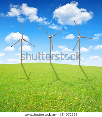 Spring meadow with wind turbines against the blue sky  - stock photo
