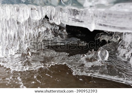 Spring melting of ice. Icicles and flow of water.