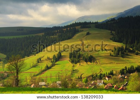 Spring morning rural landscape in the Carpathian mountains. Dramatic sky before dawn.