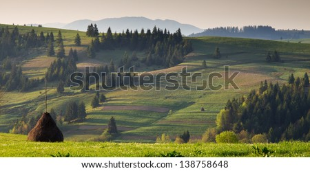 Spring morning rural landscape with a haystack in the Carpathian mountains
