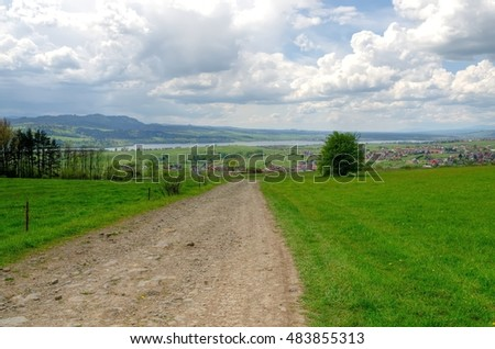 Spring mountain landscape. Rural gravel road from the river, mountains and village in the background.