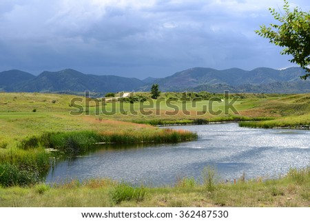 Spring Mountain Pond - Spring storm coming over a small mountain pond. - stock photo