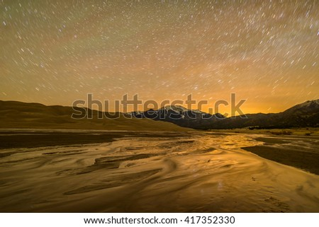 Spring Night at Great Sand Dunes National Park - Long exposure captures star trails in night sky above spring Medano Creek,  snow-capped peaks and sand dunes at Great Sand Dunes National Park. - stock photo