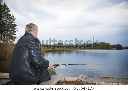 Spring on the lake fisherman with a fishing pole sitting on a wooden pier.
