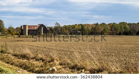 Spring On The Midwestern Farm.  Furrows in a freshly planted field with a traditional weathered and worn barn in the background. - stock photo