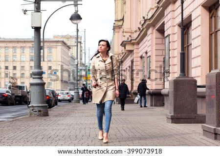 Spring on the streets of Moscow. A beautiful young girl with dark curly hair walking in stylish beige raincoat. Solar warm spring weather
