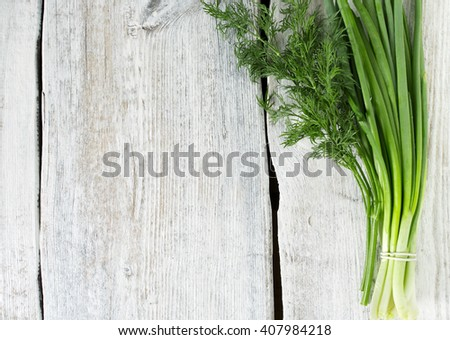 spring onion and fresh dill on wooden surface - stock photo