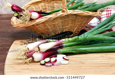 Spring onions, cebollitas cambray, both in a basket and on a cutting board being prepared for use.