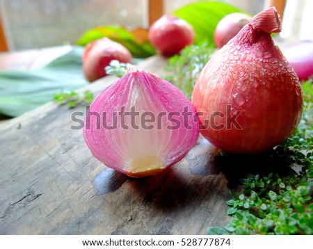 Spring Onions on wooden cutting board with window light.