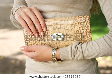 spring outdoor fashion young woman hold beige purse clutch in hand  - stock photo
