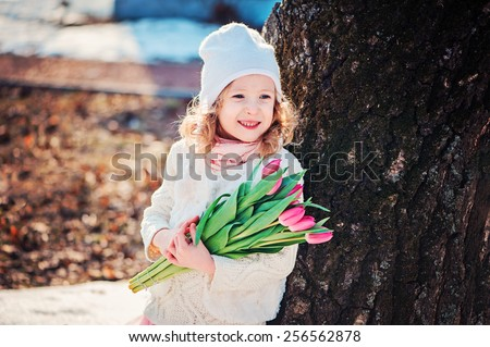 spring outdoor portrait of happy child girl with bouquet of tulips in sunny day - stock photo
