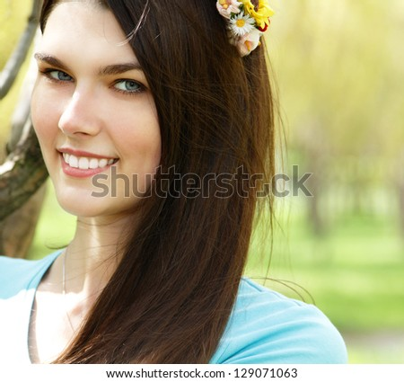 spring outdoor portrait of young cheerful attractive woman with long brown hair