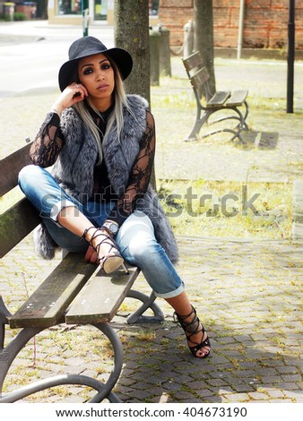 Spring outfit - beautiful african italian woman with granny hairstyle, ripped jeans, hig heels sandals, lace shirt, black hat, leather bag and fur vest.