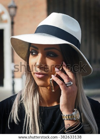 Spring outfit - Portrait of a young pretty woman calling with a smart phone, with granny hairstyle, wearing black jacket and sweater and hat