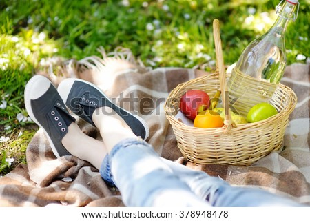 Spring picnic concept. Picnic basket with fruits, flowers and water in the glass bottle  - stock photo