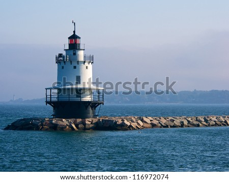 Spring Point Ledge Lighthouse with Portland Head Lighthouse in background on foggy day - stock photo
