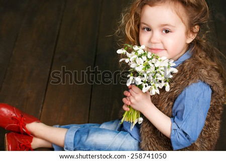 spring portrait girl with bouquet of flowers. Child with white snowdrops. studio portrait.  - stock photo