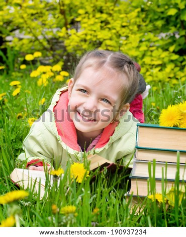 spring portrait of a cute little girl reading a book outdoors