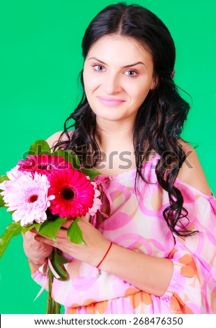 Spring portrait of a pretty young brunette with a bunch of gerberas over green background - stock photo