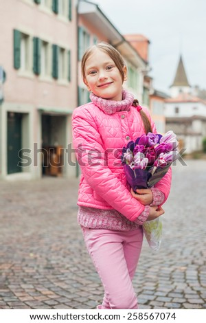 Spring portrait of adorable little girl of 7 years old, wearing bright pink coat, holding beautiful bouquet of tulips - stock photo