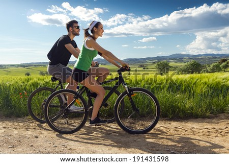 Spring portrait of  Happy young  couple on a bike ride in the countryside - stock photo