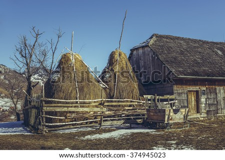 Spring rural scene with traditional Romanian farm with wooden barn, haystacks and large sleigh in Magura village, Brasov county, Transylvania region, Romania.