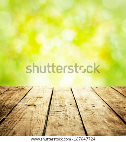 Spring rustic template background with text space. Old vintage planked wood table in perspective on fresh bright green bokeh - outdoor in the garden during sunny day. - stock photo