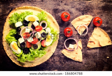 Spring salad with feta cheese on liban bread from above  - stock photo