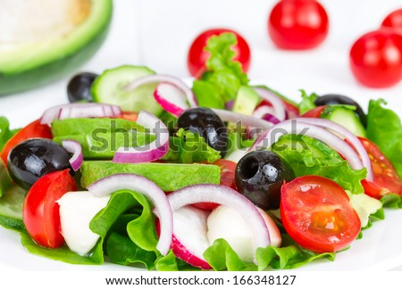 Spring salad with fresh vegetables on a white plate