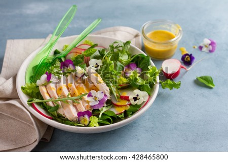 Spring salad with radishes, chicken breast and edible flower, selective focus