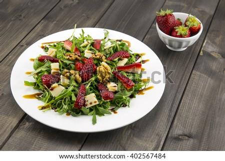 Spring salad with strawberries, rocket salad, parmesan cheese, walnuts and balsamic vinegar. - stock photo