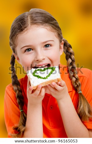 Spring sandwich - lovely girl eating cottage cheese with chives on bread