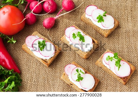 Spring sandwiches with ingredients - radish, tomato, cream, pepper, parsley, on sackcloth background, top view - stock photo