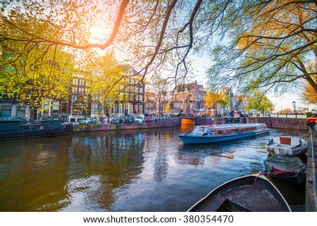 Spring scene in Amsterdam city. Tours by boat on the famous Dutch canals. Colorful evening landscape in Netherlands, Europe. - stock photo