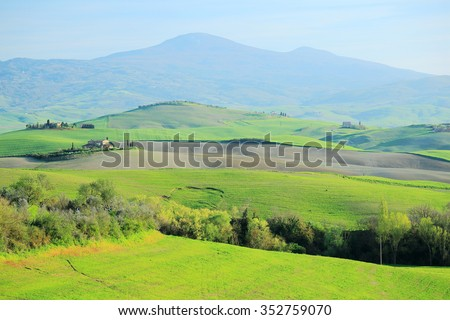 Spring scenery of idyllic Tuscany with green rolling hills in the foreground and distant mountains in the background ~ Beautiful green fields on a sunny day, in Val d'Orcia, Siena, Tuscany Italy - stock photo