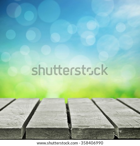 Spring sky with sunny field and  wooden table for object or picnic - stock photo