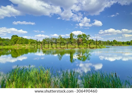 Spring summer landscape blue sky clouds river pond green trees countryside grass Poland - stock photo