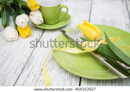 Spring table setting with fresh tulip on white wooden table