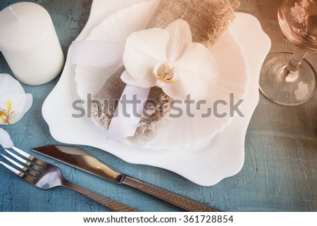 Spring table setting with orchid decorations, candles, wineglass on a vintage  background. Top view. Tinted.  - stock photo