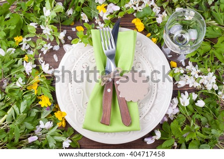 Spring table settings with flowers, cutlery and wineglass. Floral wedding table settings in rustic style. Holidays background. Top view - stock photo