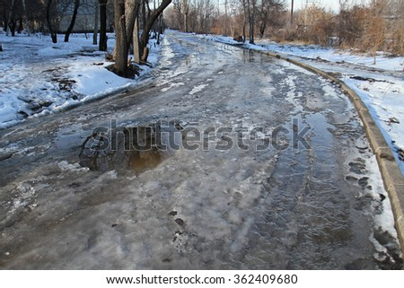 Spring thaw on a curved road. The dangerous bend in the road during icy conditions. - stock photo